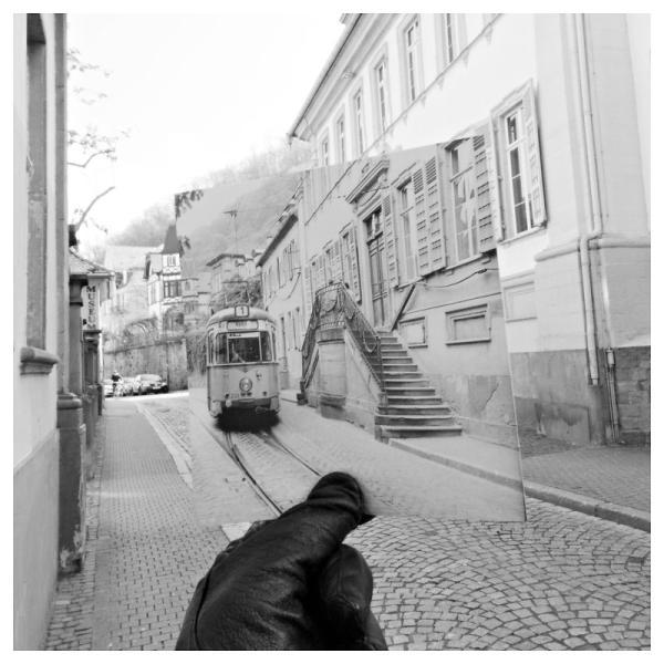 Blick in ein Foto des Hauses Buhl, in der Hauptstraße Heidelberg. Eine Hand hält ein altes Foto der gleichen Postition hinein. Eine Straßenbahn die damals fuhr ist zu sehen.