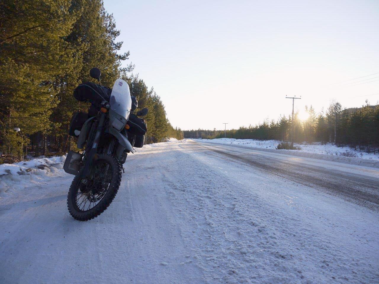 Ein Motorrad steht an einer schneebedeckten Straße, die Sonne steht tief.