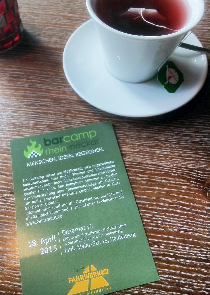 Eine Tasse mit Teebeutel darin und ein Flyer des Barcamps stehen auf einem Holztisch