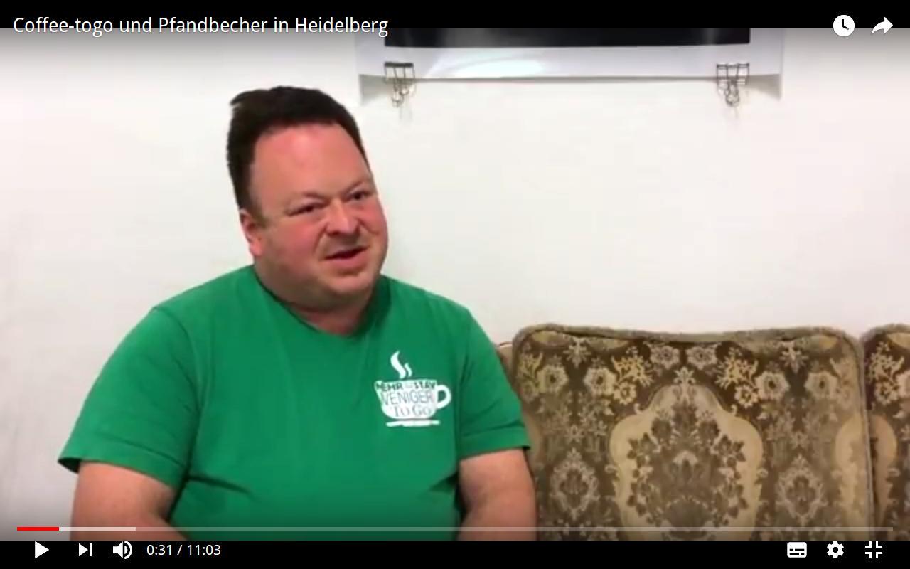 Eine Person sitzt auf einem Sofa und spricht in die Kamera