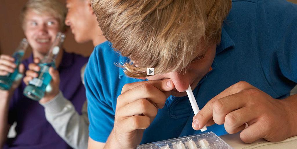 Ein junger Mann zieht eine Line mit einem Röhrchen in das Nasenloch und hält sich das andere zu