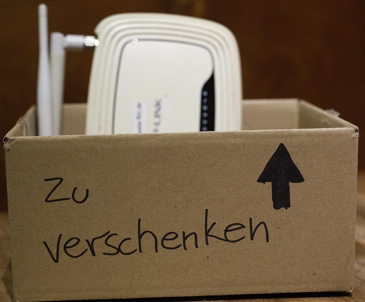 """Ein Karton auf dem """"zu verschenken"""" steht. Darin ist ein Router zu sehen."""