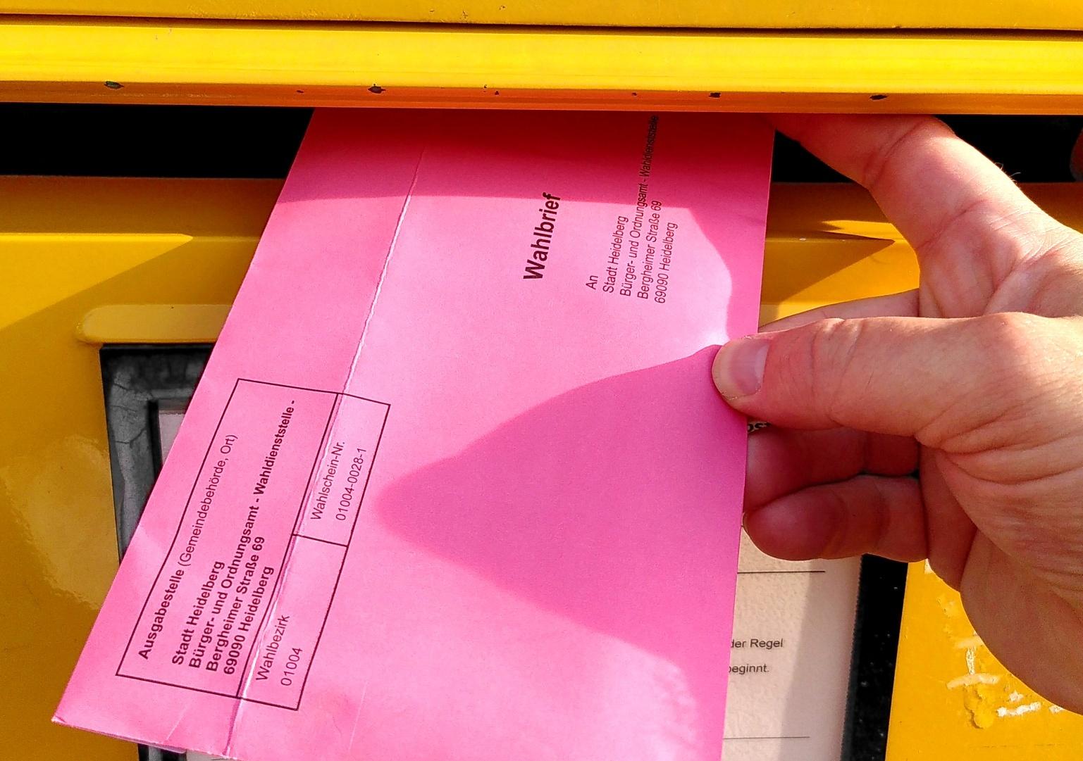 Wahlbrief, der in einen Briefkasten eingeworfen wird