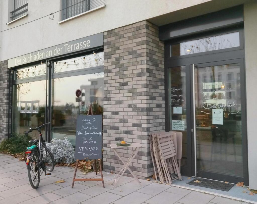 Der Buchladen von außen. Davor steht ein Fahrrad und eine Tafel.