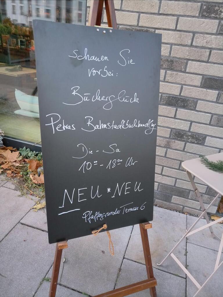 Eine Tafel informiert über den Laden und die Öffnungszeiten.