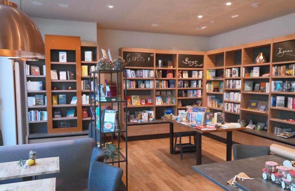 Regale gefüllt mit Büchern. Links davon Tische zum Sitzen.