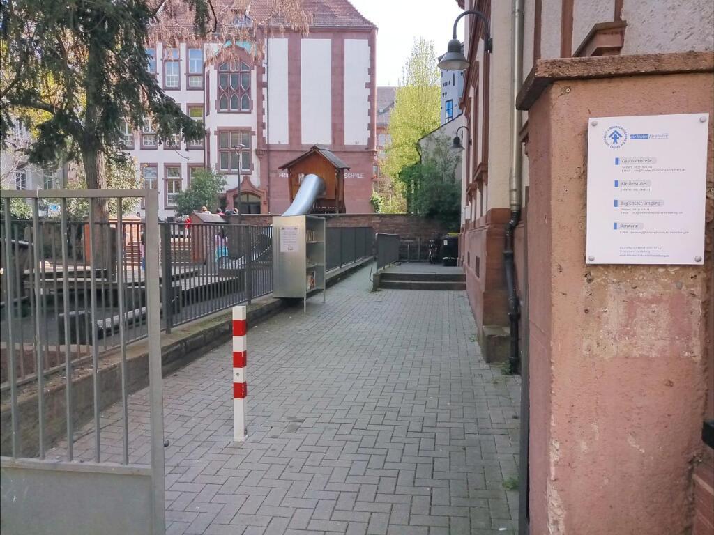 Eingang des Kinderschutzbundes und Blick auf das Bücherregal. Dahinter die Grundschule.