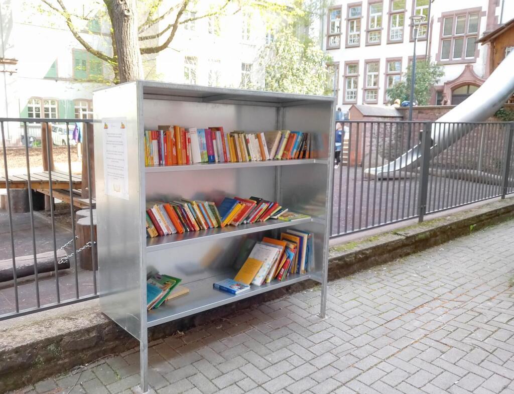 Ein offener Bücherschrank aus Metall. Es gibt drei Fächer die gut mit Büchern gefüllt sind.