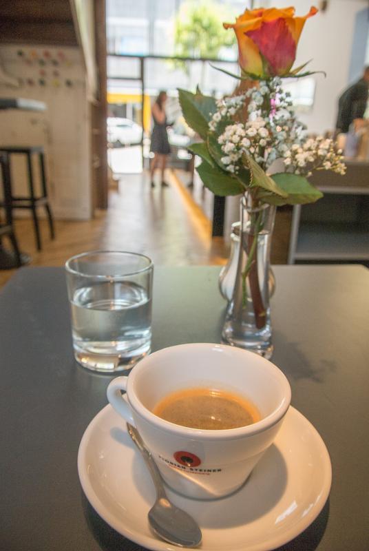 Rose, Kaffeetasse mit Espresso auf einem Tisch.