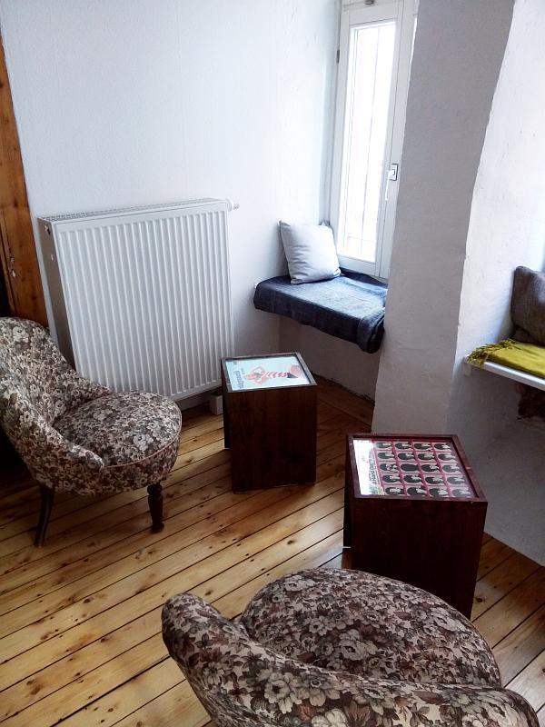 Holzdielen, zwei Sessel, zwei Tische. Zusätzlich kannst Du auf den Fensterbänken sitzen. Diese sind mit Kissen ausgestattet.