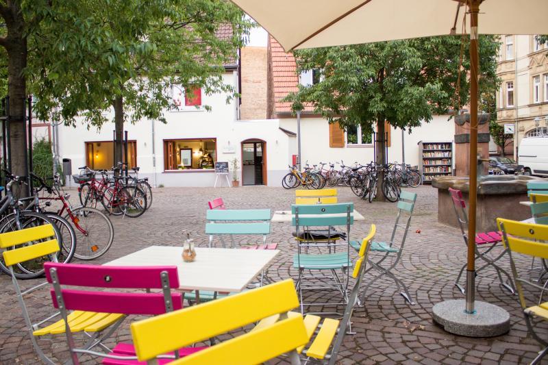 Blick von der Außenbestuhlung auf den Eingangsbereich des Cafés. Rechts der Brunnen und das öffentliche Bücherregal.