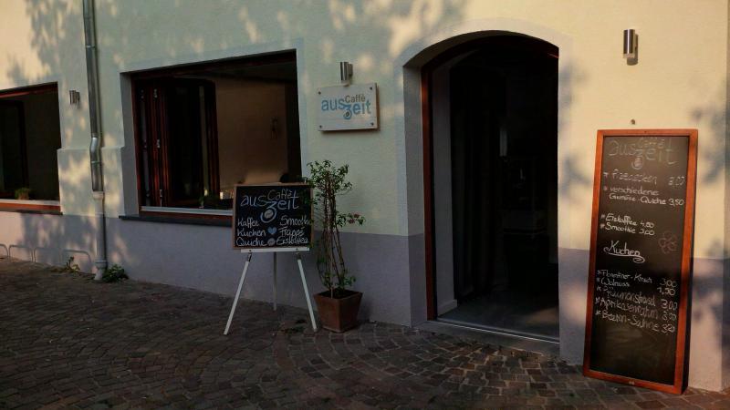 Eingang des Caffè Auszeit. Davor stehen Tafeln mit dem Tagesangebot.