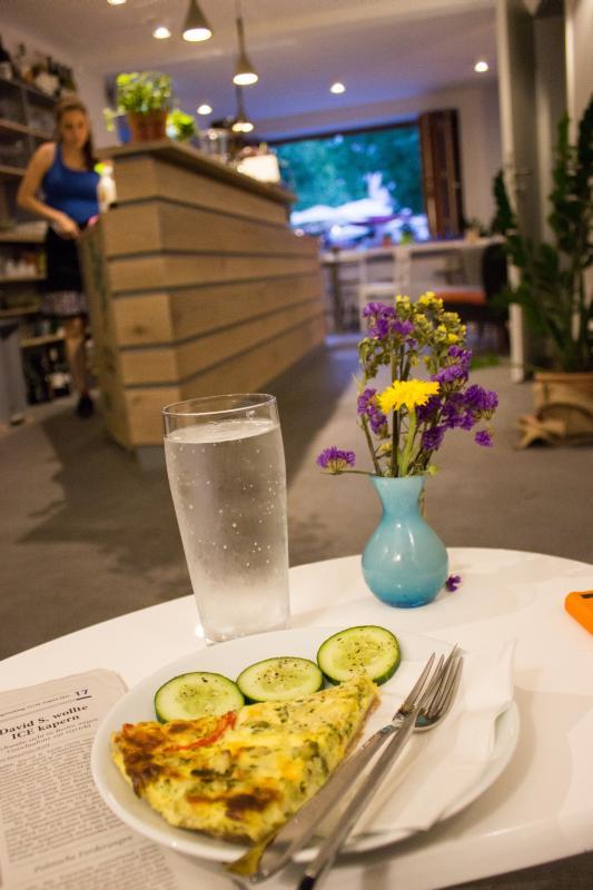 Blick auf einen Teller mit einer angerichteten Quiche und einem großen Glas Mineralwasser.