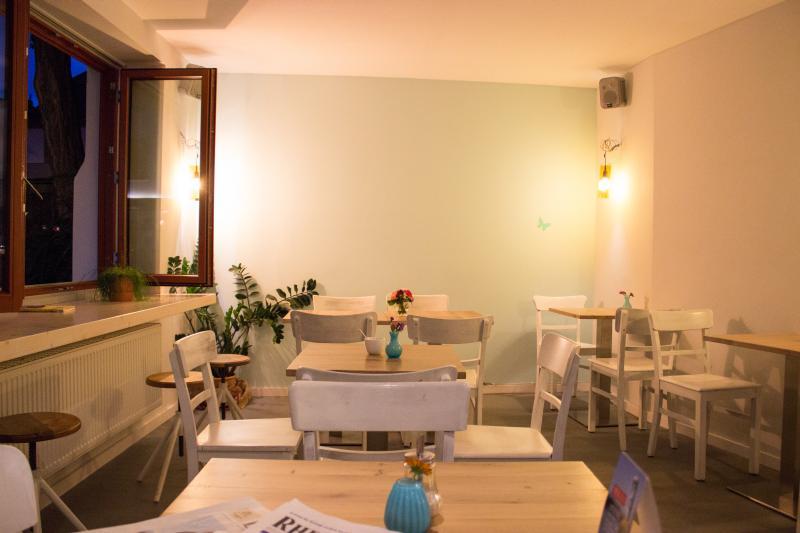 Innenraum des Caffè Auszeit mit soliden Stühlen und Tischen.