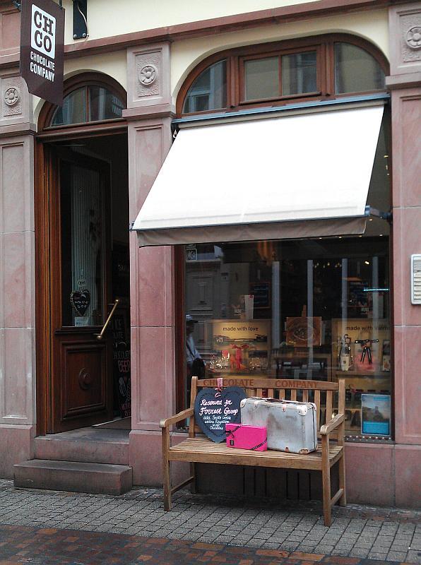 Blick auf das Schaufenster und den Eingang des Ladens. Davor steht eine Holzbank mit einem Koffer und einem Schild. Darauf steht: Reserved for Forrest Gump.