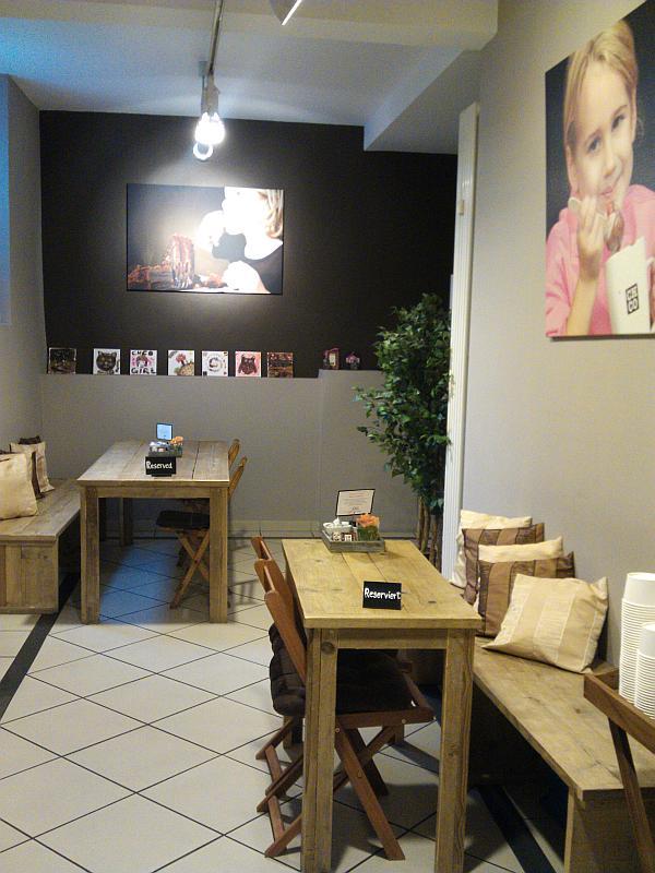 Blick in das Nebenzimmer, Zwei langezogene Holztische mit Bänken, Großformatige Fotos an den Wänden, das Thema hat mit Schokolade zu tun
