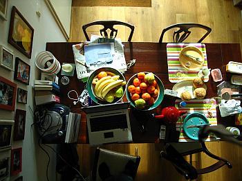 Ein gefüllter und gedeckter Esszimmertisch von oben fotografiert. Darauf steht ein Laptop, Obst, Zeitungen und Briefe, eine Lampe, Musik.