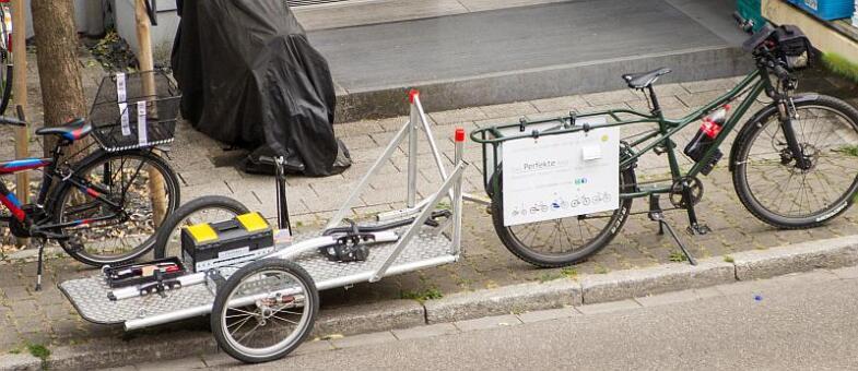 Ein Fahrrad steht am Straßenrad mit einem Radanhänger auf dem zwei Werkzeugkisten stehen