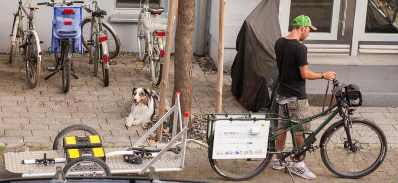 Ein Fahrrad steht am Straßenrad mit einem Radanhänger auf dem zwei Werkzeugkisten stehen. Ein Mann steh telefonierend dahinter. Ein Hund ist zu sehen.