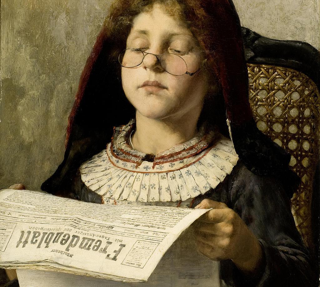 Ein Mädchen liest über eine Nickelbrille blickend in einer Zeitung