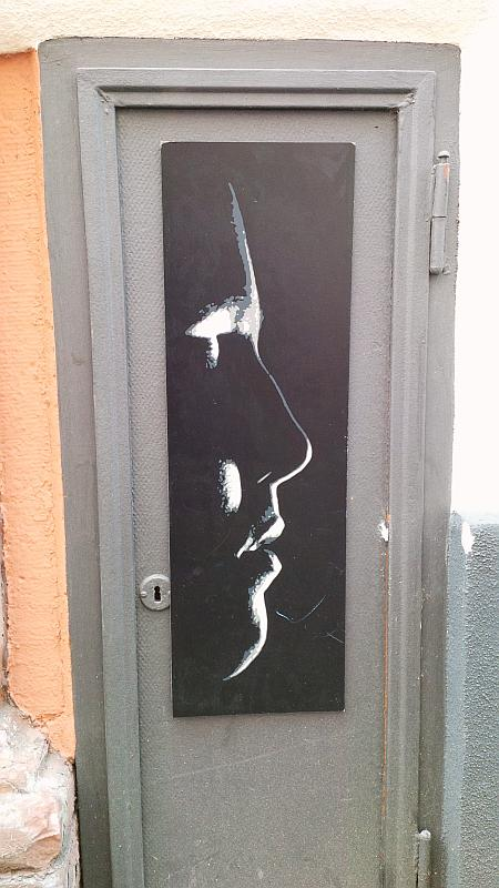 Schwarze Tafel an einer kleinen Türe in der Ingrimstraße, Heidelberg-Altstadt, mit einem weiß in Konturen gezeichneten Gesicht von der Seite.