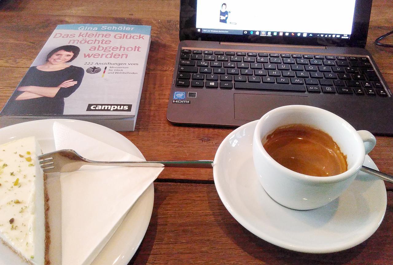Ein Laptop, ein Stück Kuchen, ein Espresso und das Buch auf einem Holztisch