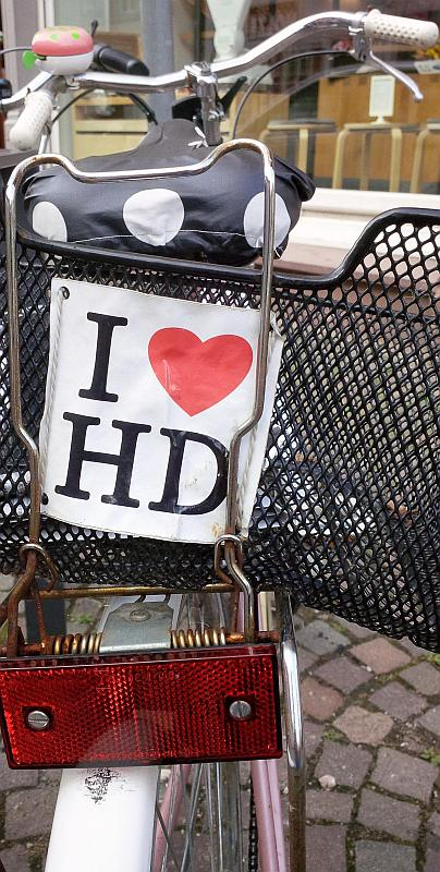 """Damenrad, am Korb des Gepäckträgers ist ein Schild mit der Aufschrift: """"I love HD"""""""
