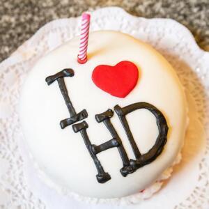 """Eine weiße Torte mit einer Kerze und einer schokoladigen Aufschrift """"I love HD"""""""