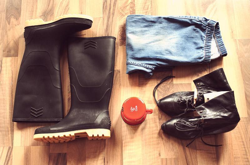 Gebrauchte Gummistiefel, Schuhe, Kopfhörer und eine Hose liegen auf einem Holzfußboden