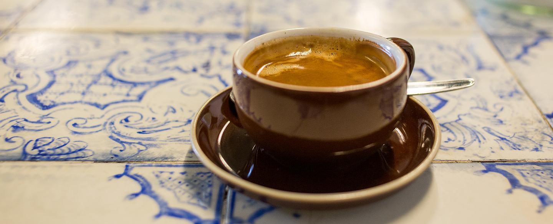 Eine Kaffeetasste mit einem Kaffee steht auf einemTisch mit weiß blauen Kacheln