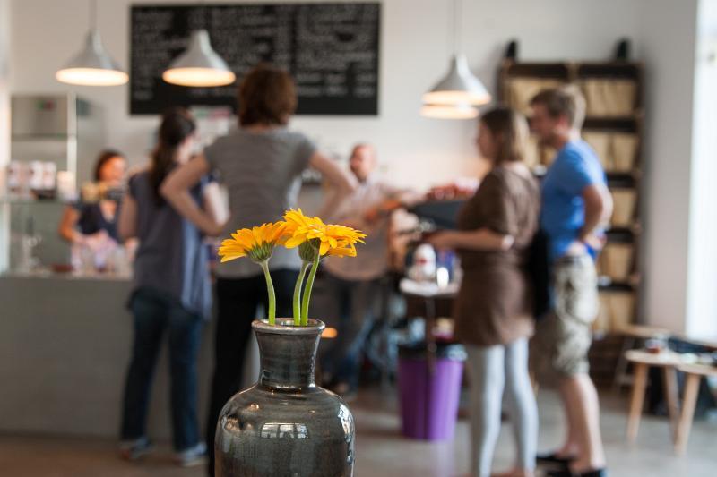 im Vordergrund eine Vase mit einer Sommerblume in gelb. Im Hintergrund unscharf Menschen an der Theke