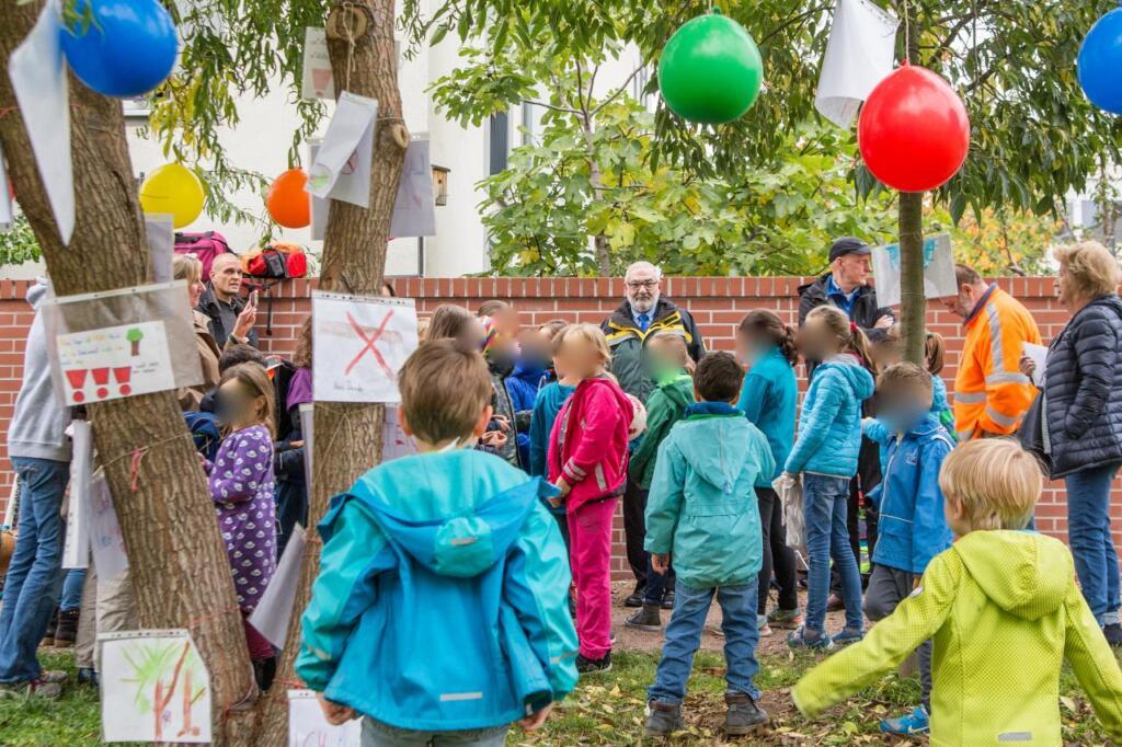 Kinder stehen Zwischen den Bäumen und dem Bürgermeister.