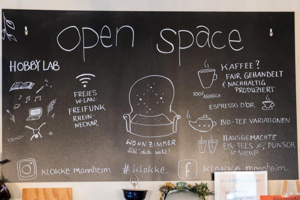 """Eine schwarze Tafel mit der Aufschrift Open Space. Unter einem Stuhl steht """"Wohnzimmer fühl dich wohl!"""". Es gibt weitere Infos zu den Getränken und Social Media."""