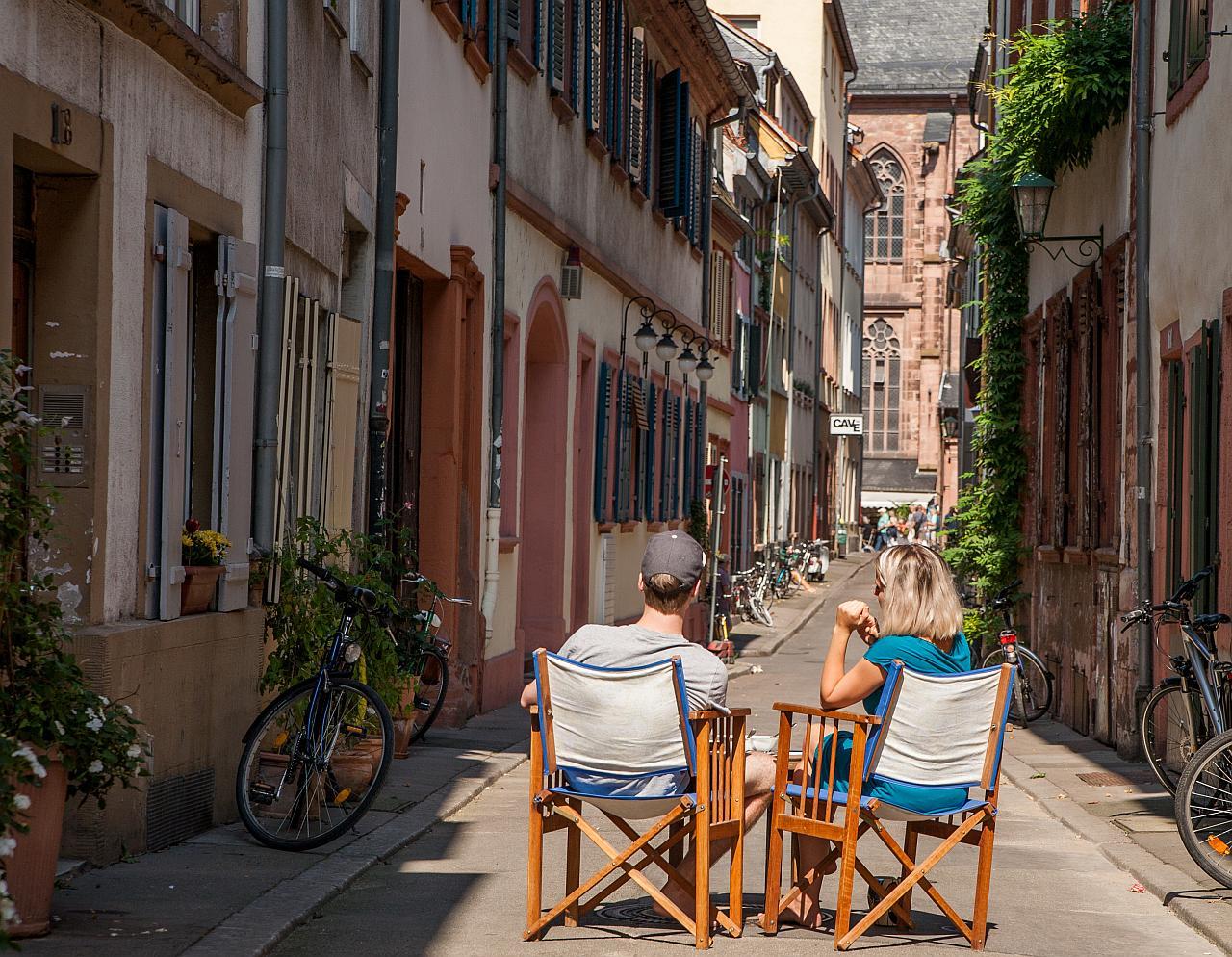 Zwei Junge Menschen sitzen mit Tisch und Stühlen mitten auf der Gasse in der Altstadt
