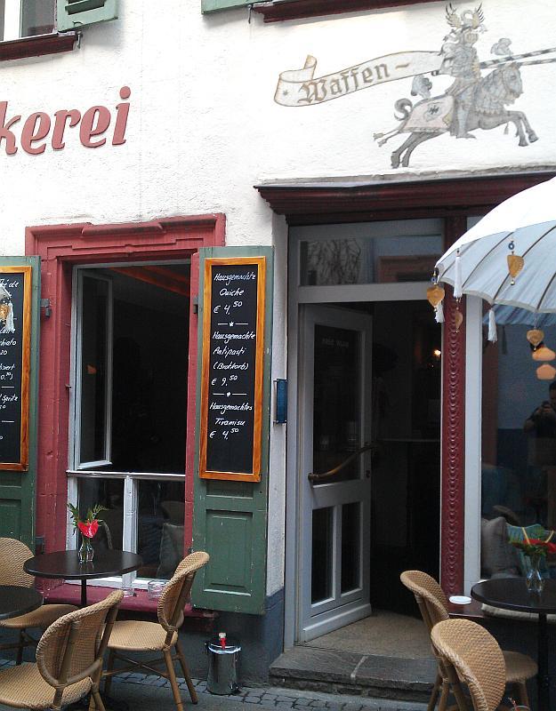 Eingang in das Café. Rechts und Links stehen Tische und Stühle. Am Eingang hängt eine Tafel, auf der eine Quiche, ein Antipasti und ein Tiramisu angeboten werden.