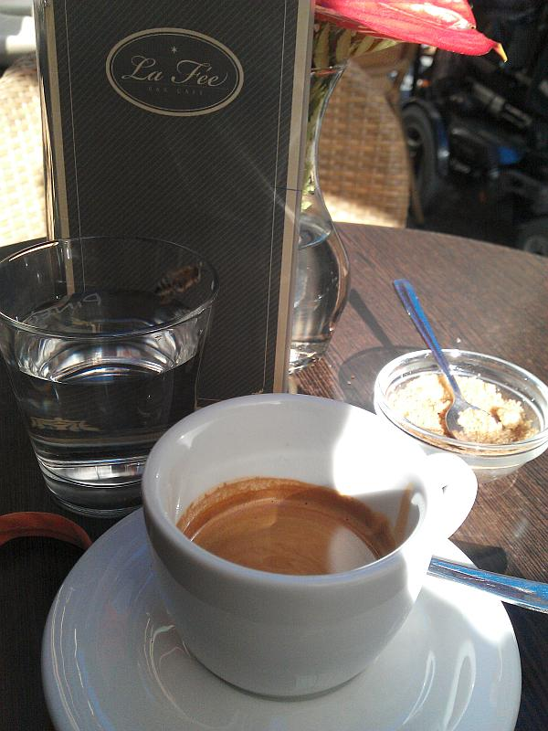 Doppelter Espresso in einer weißen Tasse mit einem Glas Wasser und braunem Zucker. Dahinter die Getränkekarte.