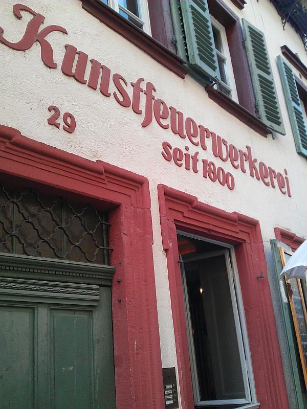 """Schriftzug """"Kunstfeuerwerkerei"""" am Haus. Foto schräg nach oben."""