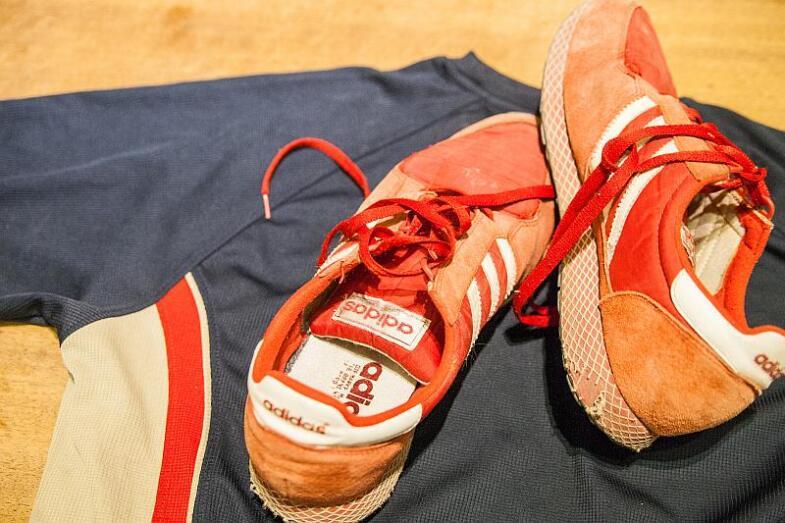 Rote Laufschuhe mit drei weißen Streifen liegen auf einem Laufshirt