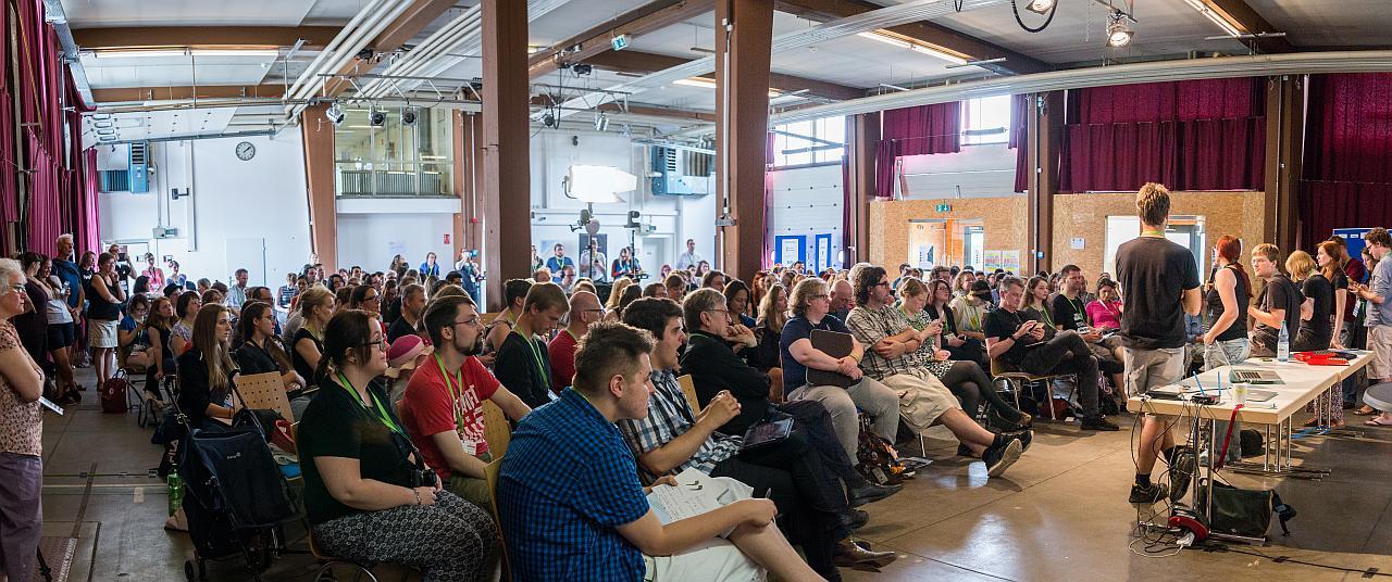 Panorama von der Begrüßung. Viele Menschen sitzen in einem großen Saal und werden vom Orateam begrüßt