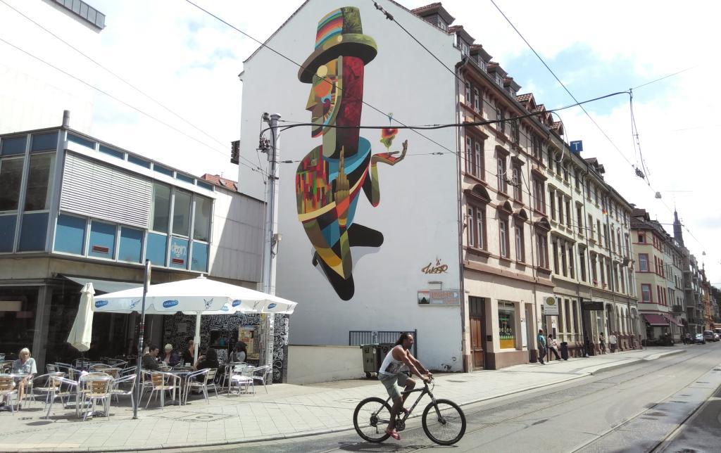 Eine goße Wanmalerei an der Hauswand. Am Fuße der Malerei ist ein Café