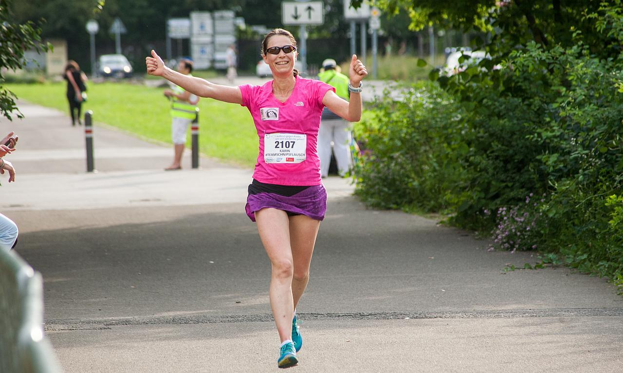 Karin Schumacher mitten im Lauf. Sie streckt die Daumen nach oben.