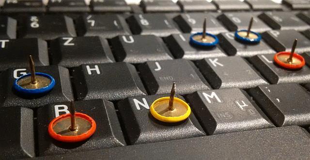 Tastatur mit Reißnägeln auf einigen Buchstaben