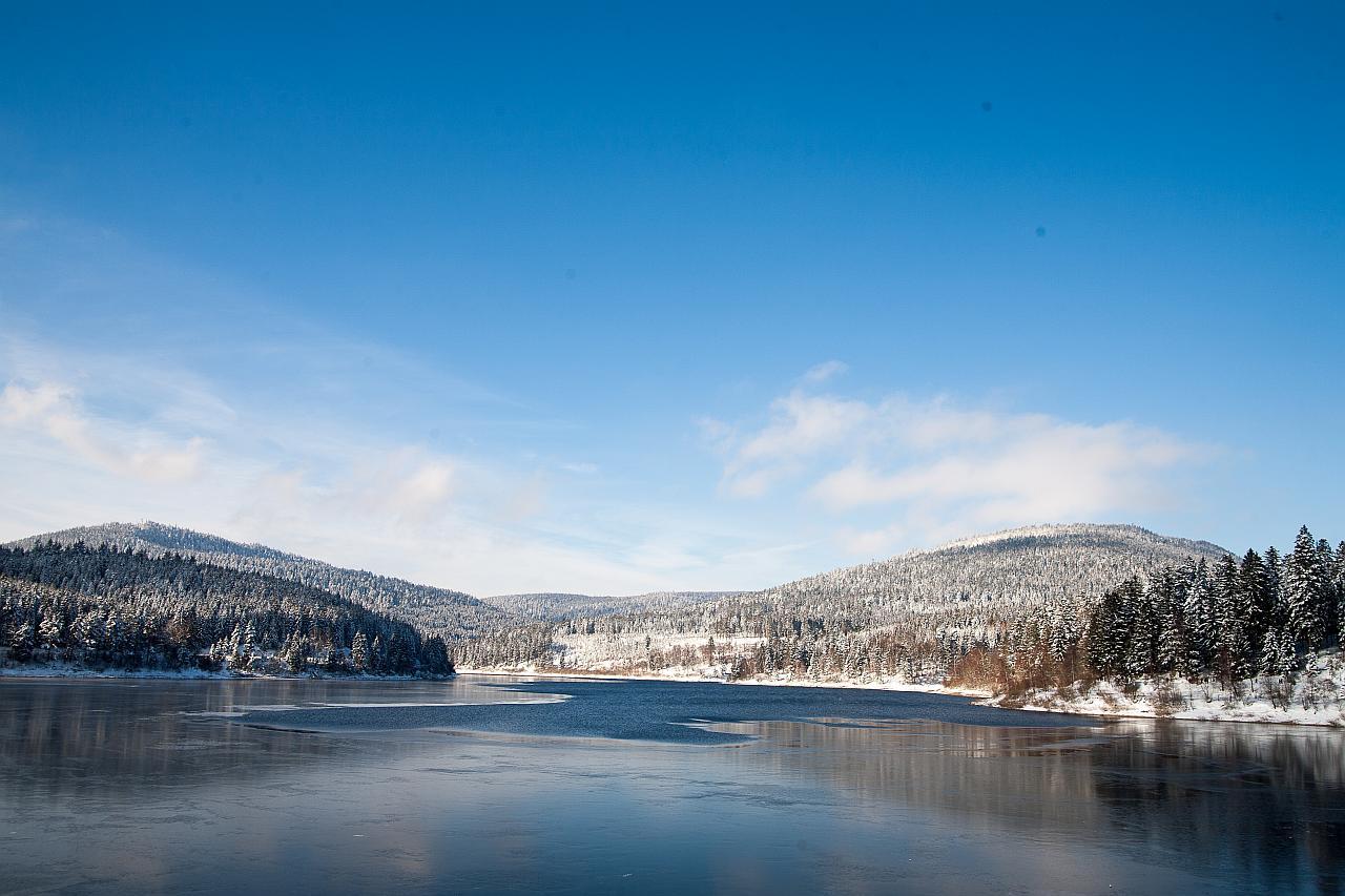 Stausee im Winter. Das Ufer ist schneebedeckt.