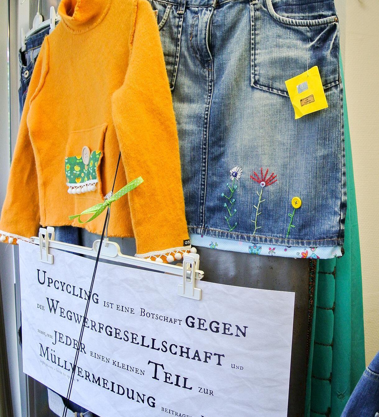 Ein orange Pulli und eine Jeans hängen an einer Wand. Darunter ein Schild mit der Aufschrift Upcycling ist eine Botschaft gegen die Wegwerfgesellschaft...