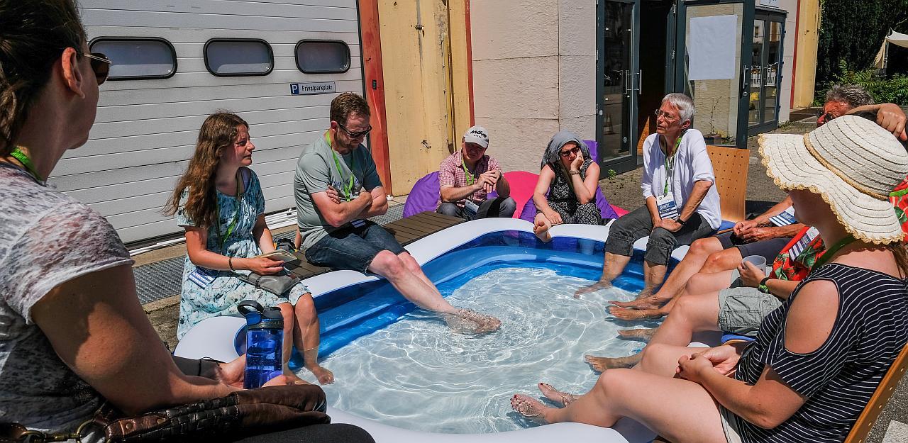 Teilnehmende sitzen zu einer Session in und um ein Planschbecken.