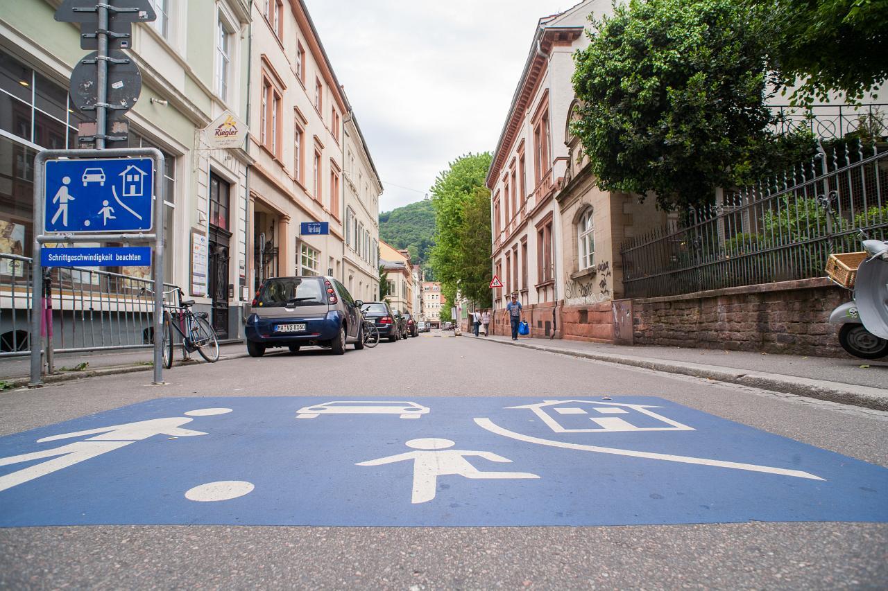 Theaterstraße. Ein Schild und ein auf dem Boden aufgemaltes Schild zeigen an, dass dies eine Spielstraße ist. Also auf 7 km/h begrenzt.