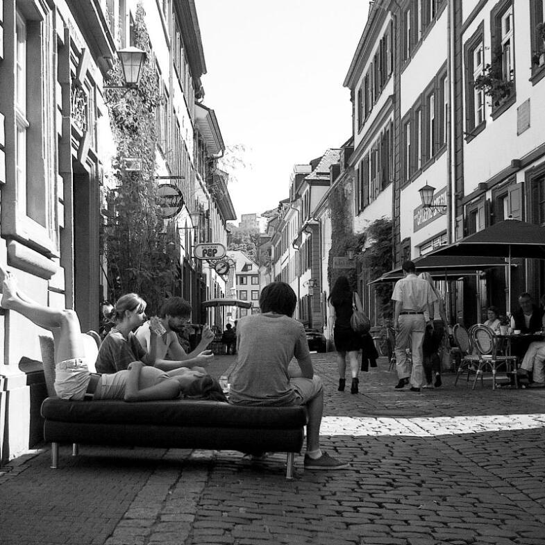 Mitten in der Altstadt haben einige Bewohner ihre Couch auf das Kopfsteinpflaster getragen und lassen sich gemütlich dort nieder - Foto in Schwarz-Weiß