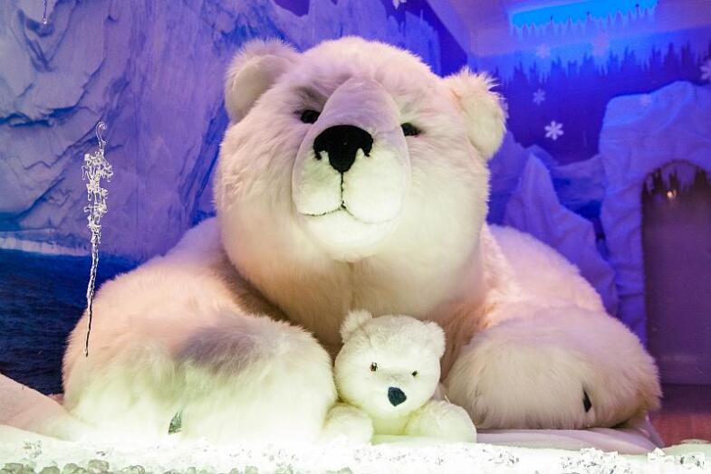 Blick in ein eisig gestaltetes -Schaufenster in dem ein riesiger Kuschel-Eisbär mit seinem Baby liegt.