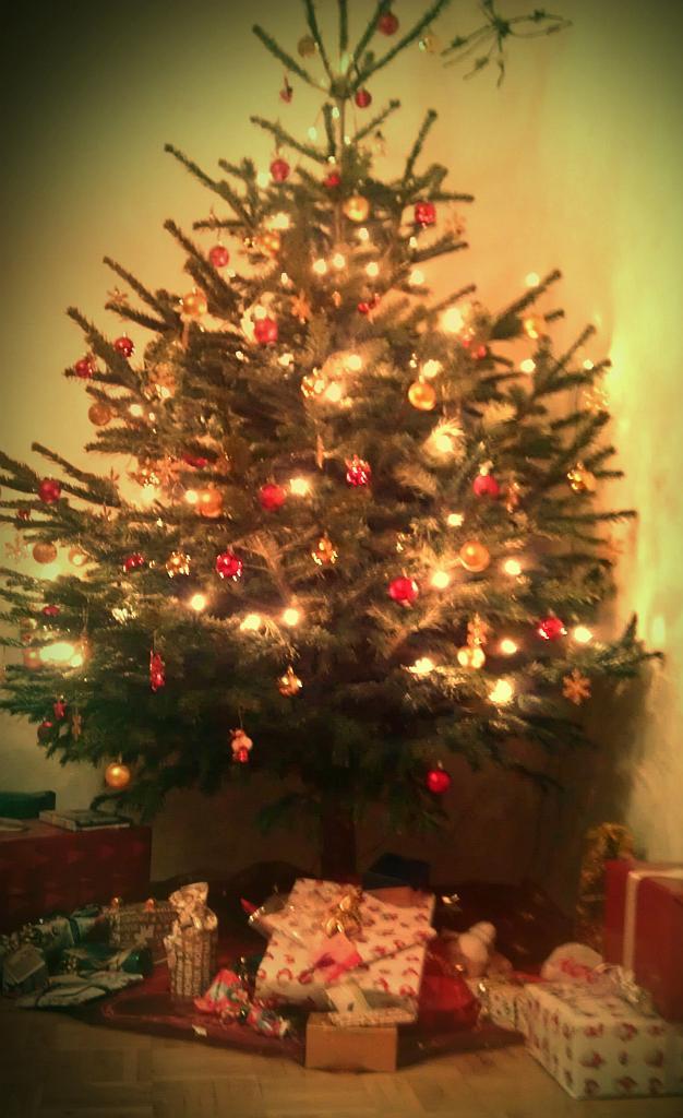 Foto eines Weihnachtsbaumes mit Geschenken darunter