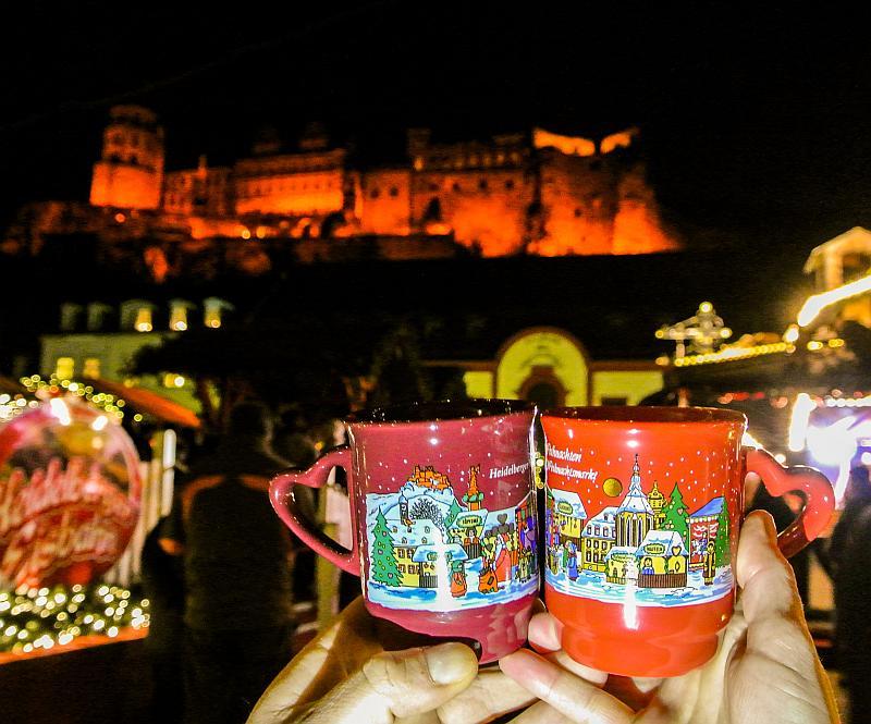 Zwei unterschiedliche Glühweintassen aus dem Jahr 2015, dahinter das Heidelberger Schloss